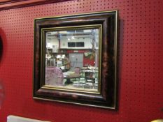 A modern square form bevelled edge mirror with cushion form frame,