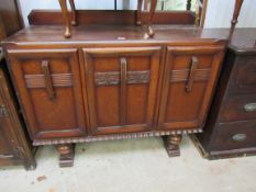 A 1940s oak three door sideboard with drawers to interior