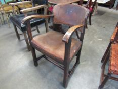 An Arts & Crafts oak desk chair with brass studded leather upholstery
