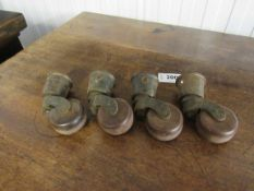 A set of four brass and brown porcelain table castors