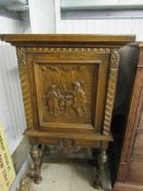 A small Continental carved oak cupboard on stand