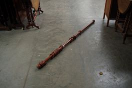 A timber curtain pole and rings,