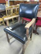 A 1930s oak framed elbow chair with leather seat and back