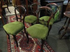 A set of four Victorian walnut balloon back dining chairs, sprung stuffed serpentine front seats,
