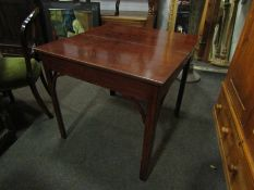 A mahogany tea table with arched supports,