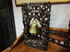 An early 20th Century Chinese hardwood carved and inlaid temple bell stand with brass bell,