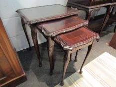 A nest of three reproduction mahogany coffee tables with glass tops