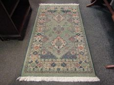 A Gabbeh green ground wool rug, central row of three guls and multiple borders, 3' x 4.5' approx.