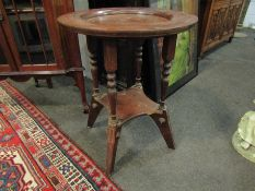 A late 19th Century oak pub table with spindle supports