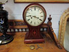 A Victorian mahogany inlaid balloon form striking mantel clock, with pendulum and key,
