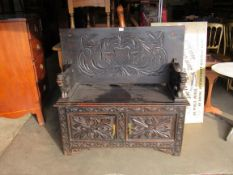 An Edwardian carved oak monks bench, with lift up seat,