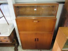 A 1950's mahogany bookcase with sliding glass top over a fall front and fitted interior,