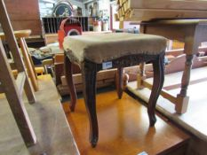 A carved upholstered stool