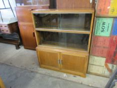 A 1940's/50's honey oak bookcase with two sections of sliding glass doors over two enclosed doors