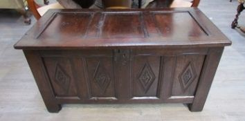 A circa 1700 panelled oak coffer with lidded internal candle box and carved lozenge decoration over