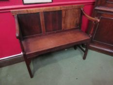 An early 20th Century slender oak settle with panel back,