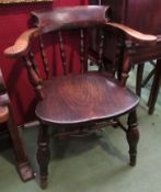 A late 19th/early 20th Century captains smokers bow chair with spindle back,
