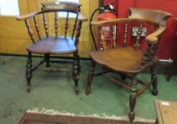 A near pair of late 19th/early 20th Century elm seated captains chairs with turned spindle backs,