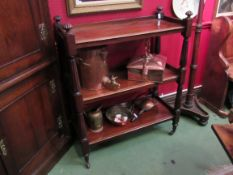 A Victorian mahogany three tier buffet with melon fluted finials on castors,