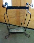 A wrought metal black painted stick stand with scroll detail and drip tray,