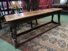 A 19th Century elm topped long stool/bench with carved and turned legs to H-stretcher,
