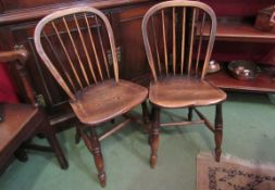 A pair of late 19th Century stick back elm seated chairs with sunken seats,