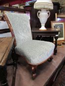 An early Victorian walnut nursery open armchair with carved acanthus leaf scroll back rest over