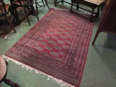 A red ground rug with geometric borders,