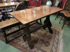 A small oak trestle table with shaped stretcher,