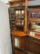 In the manner of Maple & Co a Victorian mahogany mirror back corner cabinet with turned finials and
