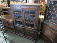 An Old Charm style oak lead glazed four door cabinet with linen fold panels,