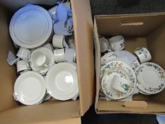 A box containing white and gilt tableware, including cups, saucers,