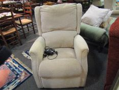 A beige chenille upholstered reclining electric armchair