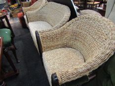 A rush and cane conservatory three piece suite with swirled design cushions