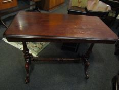 A Victorian mahogany stretcher table with brass castors and turned supports,
