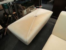 A cream upholstered pouffe