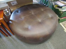 A large leather round pouffe,