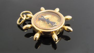 An 18ct gold charm compass in the form of a ships wheel, 12.