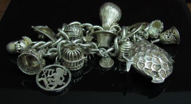 A silver charm bracelet hung with various charms including pear, sailboat, beehive, fish etc, 95.