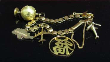 A gold bracelet (unmarked) hung with various charms including 9ct helicopter, aeroplane,