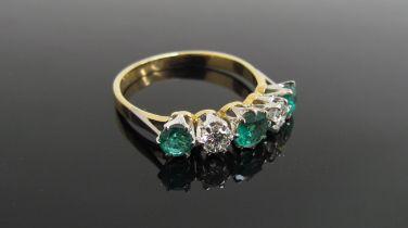 An emerald and diamond five stone ring, stamped 750/plat, .40ct diamond, .90ct emerald.
