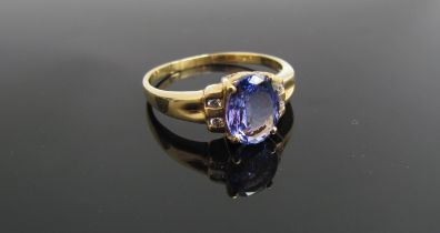 An 18ct gold tanzanite ring, the oval stone flanked by diamonds. Size R, 3.