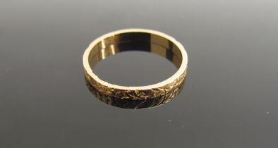 An 18ct gold band, engraved pattern. Size P, 2.