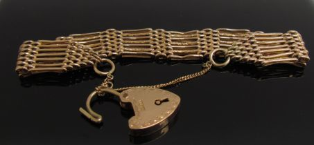 A 9ct gold seven bar gate bracelet with engraved padlock clasp, 23.