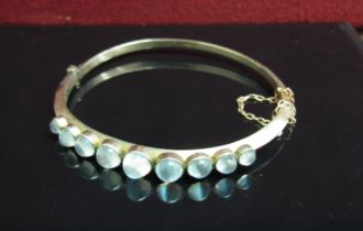 A 9ct gold stiff hinge bangle with graduated cabochon moonstones, stamped 9c, 8.