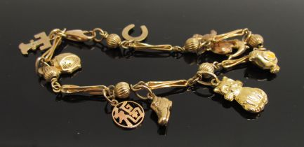 A 9ct gold charm bracelet set with nine charms including cat, chick, rabbit, horseshoe,