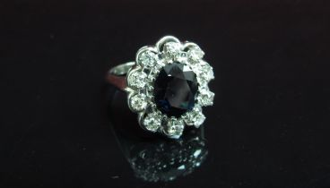 A white gold sapphire and diamond cluster ring, shank stamped 18k. Size R, 6.