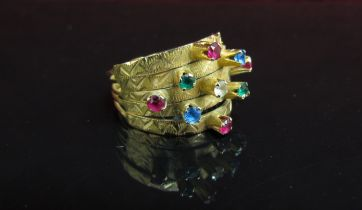 A gold ring with five bands all set with coloured stones. Size O, 4.