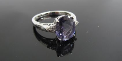 A 9ct white gold ring with oval purple stone flanked by diamond set shoulders. Size R, 3.