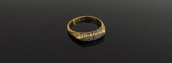 A 22ct gold ring set with five small diamonds, scroll engraved mount. Size N, 3.